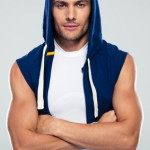 Fitness man in hood standing with arms folded