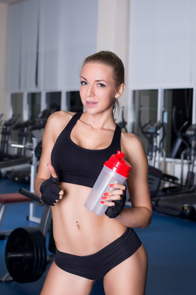 Strong fitness girl with cocktail bottle after workout in gym